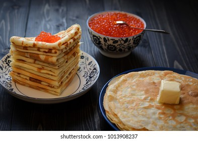 traditional thin Russian pancakes with red caviar on a dark rustic wooden background
