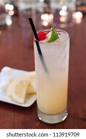 traditional tom collins served on a bar top in a tall glass with cherry and lime wedge garnish