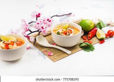 Traditional Tom Yum soup with blooming sakura branch on white stone table. Thai food concept. Copy space