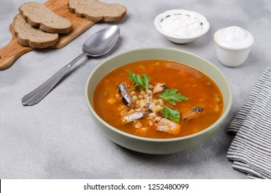 Traditional tomato fish soup with pearl barley and vegetables. Selective focus.