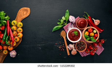 Traditional tomato ketchup sauce. Cherry tomatoes, spices, chili peppers, olive oil, parsley. Top view. On a black wooden background. Free space.
