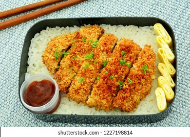 Traditional Tonkatsu breaded pork cutlet with rice, egg roll and sauce in bento box.  Horizontal format shot in natural light.