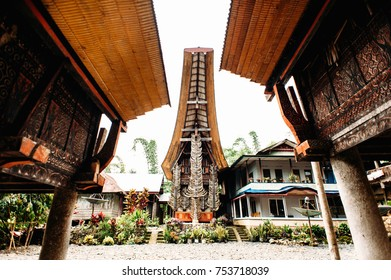 Traditional torajan building tongkonan with a lot of buffalo horns on a facade. Rice barns with carving on a foreground. Tana Toraja, Rantepao, Sulawesi, Indonesia