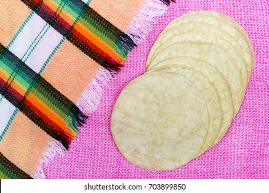 Traditional tortillas circle placed on colorful textile background.