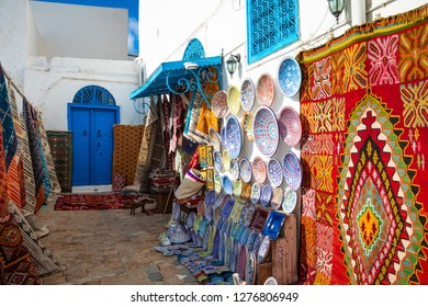 Traditional Tunesian carpets hanging on blue walls in resort town Sidi Bou Said. Tunisia, North Africa.