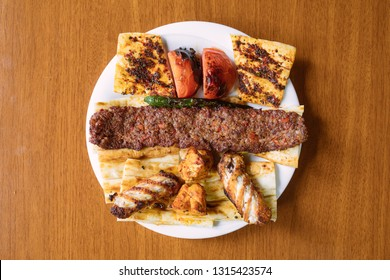 Traditional Turkish Adana kebab or kebap meat food on table from top view in turkish restaurant.