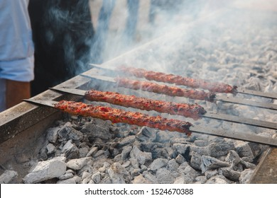 Traditional Turkish Adana Kebab or Kebap on the grill with skewers in the turkish restaurant for dinner. Turkish cuisine food culture in Turkey.
