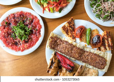 Traditional Turkish Adana Kebap with salads and appetizers. Selective Focus Turkish Cuisine Dining Dinner Table. This is Turkish food culture in Turkish Restaurant.