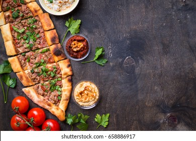 Traditional turkish baked dish pide. Turkish pizza pide, tomatoes, wooden spoon on the table. Middle eastern appetizers. Turkish cuisine. Top view. Pide with meat filling. Space for text