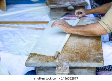 """Traditional turkish  bread. Also known as """"yufka ekmek"""" ,  natural organic homemade yufka bread. Woman rolls out dough, close-up. Making Turkish traditional bread"""