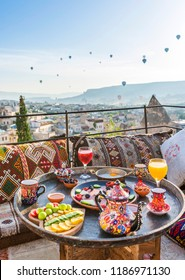 Traditional turkish breakfast with Cappadocia view and flying balloons on the background. Goreme, Turkey.