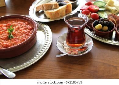 Traditional Turkish breakfast with menemen in a earthenware bowl.