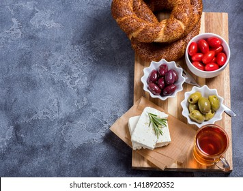 Traditional turkish breakfast with olives, simit bagels, feta cheese, tea, top view, copy space background, oriental food