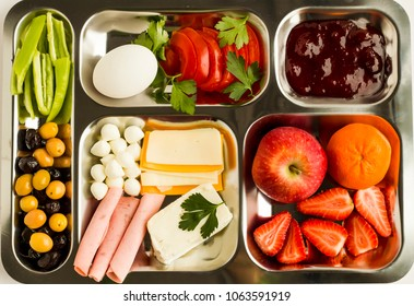 Traditional Turkish breakfast with salami, cheese, pepper, jam, egg, tomato, olives and fruits in a metal food tray (table d'hote) on white background
