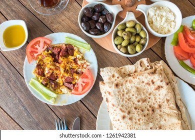 Traditional Turkish Breakfast Table. Turkish Breakfast Food Cuisine Culture. Turkish pide yufka ekmek, tea, bagel, borek, sikma, cheese, olives, oil and honey on wooden table from top view.