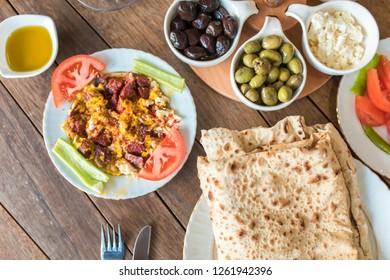 Traditional Turkish Breakfast Table. Turkish Breakfast Food Cuisine Culture. Turkish pide yufka ekmek, tea, bagel, borek, sikma, cheese, olives, oil and honey on wooden table from top view.