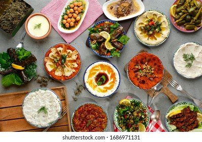Traditional Turkish celebration dinner. Flat-lay of people feasting at table full of Turkish salads, cooked vegetables, meze starters, pastries and raki drink, top view. Middle Eastern cuisine - Shutterstock ID 1686971131