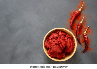 Traditional turkish chili pepper paste in bowl or spoon with dried peppers on wooden table, homemade healthy food