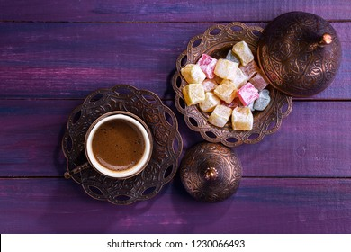 Traditional Turkish coffee  and Turkish delight on dark violet wooden background. Flat lay.