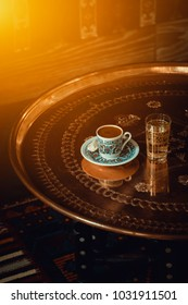 traditional turkish coffee and glass of water on retro copper tray