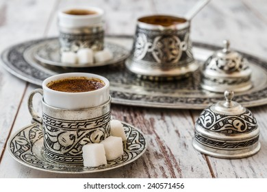 Traditional Turkish coffee in traditional silver cup with silver pot and tray