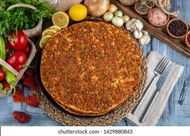 Traditional Turkish Cuisine: Lahmacun turkish delicious pizza with minced beef or lamb meat, paprika, tomatoes, cumin spice, on rustic wooden table background.