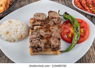 Traditional Turkish cuisine, lamb skewers, rice, ayran. On the wooden floor.