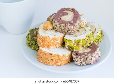 Traditional Turkish Delight Lokum on White Plate Sweet Rolls of Rahat Lokum with Nut Paste, Hazelnut, Pistachio and Sesame. Ramadan Sweets