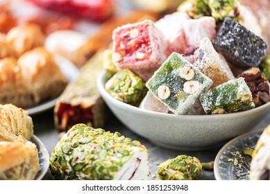 Traditional turkish delight on grey background. Arab dessert, baklava, halva, rahat lokum, sherbet, nuts, pistachios in bowl on grey background.