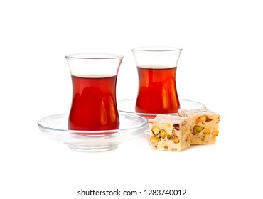 Traditional turkish delight rahat lokum with two glasses of tea on a white background