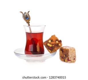 Traditional turkish delight rahat lokum with glass of tea on a white background