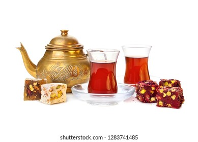 Traditional turkish delight rahat lokum with two glasses of tea and teapot on a white background