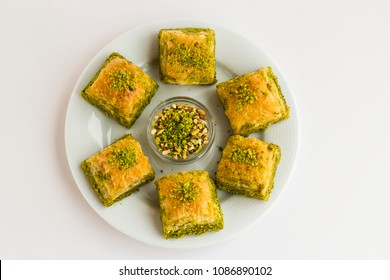 Traditional Turkish dessert,pistachio baklava in the round,white porcelain plate with pistachio nuts,on the white surface.Close up taken,top view,isolated.