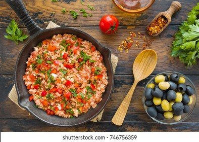 Traditional Turkish dish Menemen cooked from eggs and tomatoes in a black pan and fresh vegetables on the wooden rustic table, top view.