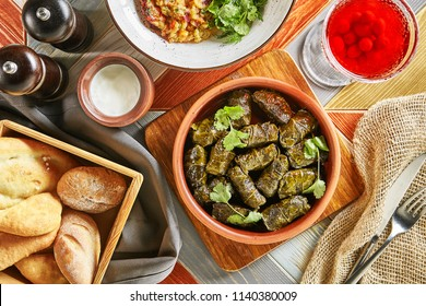 Traditional Turkish Dolma, Sarma or Dolmades with Tzatziki Sauce in Ceramic Bowl Top View. Traditional Mediterranean Dish Dolmadakia or Tolma Stuffed Grapes Leaves on Rustic Background