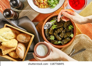Traditional Turkish Dolma, Sarma or Dolmades, Tzatziki Sauce, Fresh Bread and Hand with Spoon Top View. Eating Traditional Mediterranean Dish Dolmadakia or Stuffed Grapes Leaves on Rustic Background