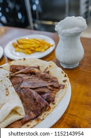 Traditional Turkish Doner Kebab, shawarma or gyros with pita rice and ayran. Turkish, greek or middle eastern style doner kebab food on wooden table background.