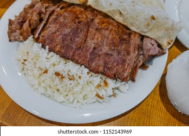 Traditional Turkish Doner Kebab, shawarma or gyros with pita and rice. Turkish, greek or middle eastern style doner kebab food on wooden table background.
