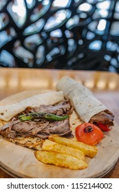 Traditional Turkish Doner Kebab, shawarma or gyros with pita. Turkish, greek or middle eastern style doner kebab food on wooden table background.