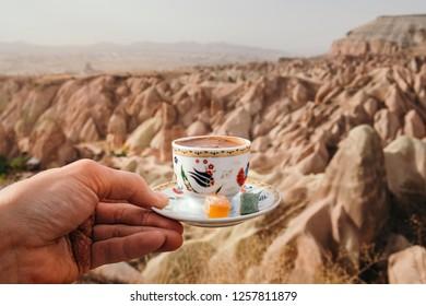 Traditional Turkish drink on rose valley landscape background in Cappadocia, Goreme