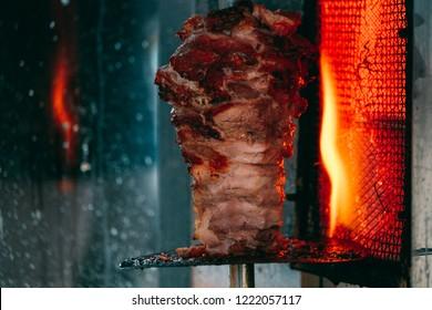 Traditional Turkish food Doner Kebab. Turnspit skewing kebap or kebab on metal skewer in the kebab restaurant. Shawarma meat being cut before making a sandwich. Shawarma meat cooking and turning