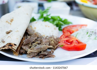 Traditional Turkish food, kebap on a white plate with rice called pilav (selective focus)