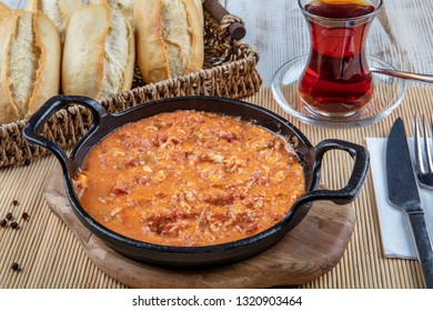 Traditional turkish food menemen made by eggs, and tomatoes. Tea.