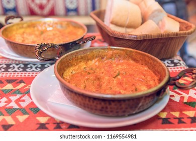 Traditional turkish food menemen in metal dishes on a multicolored tablecloth, selective focus