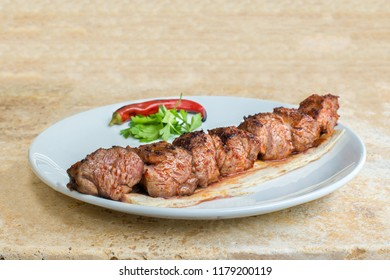Traditional Turkish Grilled Mangal Shish Skewer Kebab. Adana Kebap with salads and appetizers. Turkish Cuisine Dining Dinner Table. This is Turkish food culture in Turkish Restaurant.