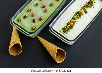 Traditional Turkish Ice Cream Maras,vanilla and pistachio in the glass containers at the black surface.