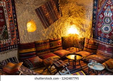 Traditional Turkish interior with vintage carpets and cushions with striped ethnic ornaments. Small round coffee table in center of corner sitting zone in Asian interior. Turkish coffee time concept
