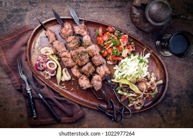 Traditional Turkish lamb kebab barbecue skewer with cabbage and tomato onion salad as top view on a plate - vintage