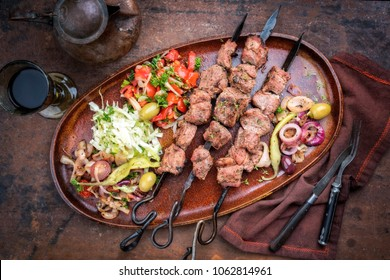 Traditional Turkish lamb kebab barbecue skewer with cabbage and tomato onion salad as top view on a plate