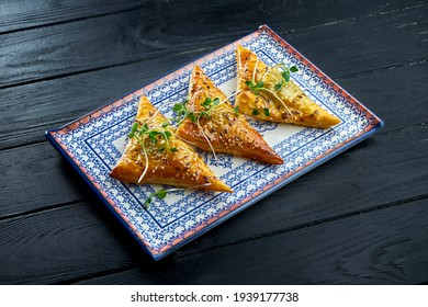Traditional Turkish meat patty - burek served on a blue plate against a dark background. B?rek made of a thin flaky dough such as phyllo or yufka, typically filled with meat. - Shutterstock ID 1939177738